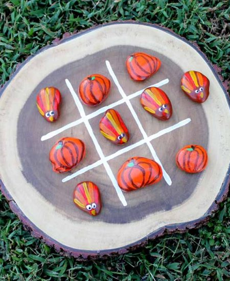 Wood slice with painted rocks for a tic tac toe game