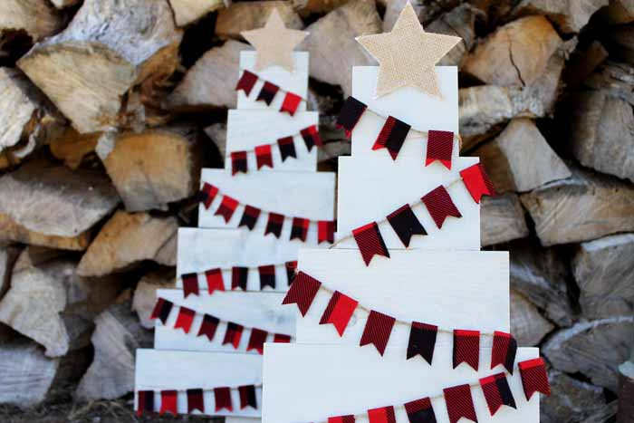 Adding a burlap star on top of a pallet Christmas tree!