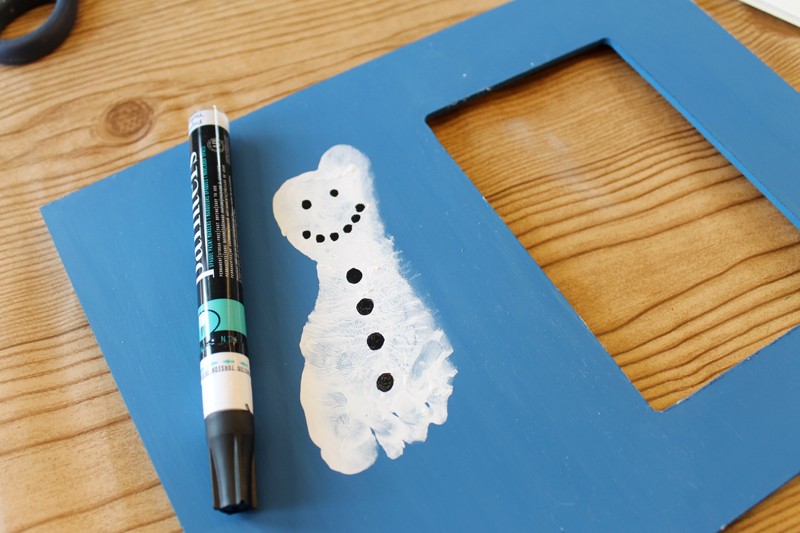 adding details to a snowman with a black paint pen
