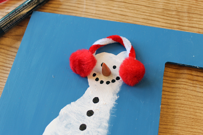 adding earmuffs to a footprint snowman