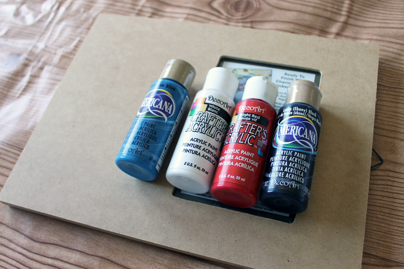 bottles of craft paint on a plain photo frame on a table