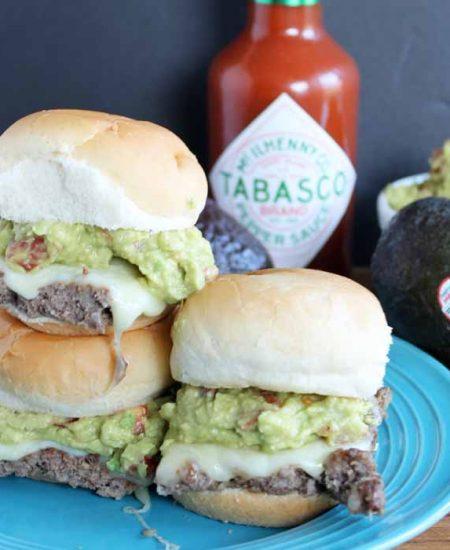 adding avocado spread to slider burgers