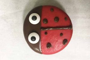 adding chocolate details to a ladybug cookie