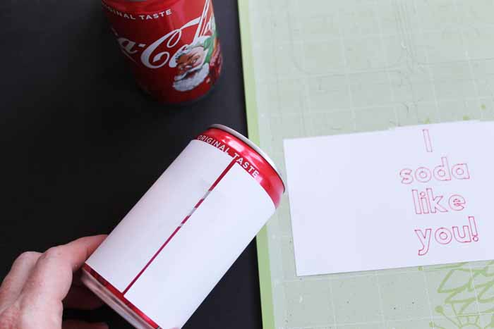 top shot showing how to tape paper to soda can for cheesy valentines