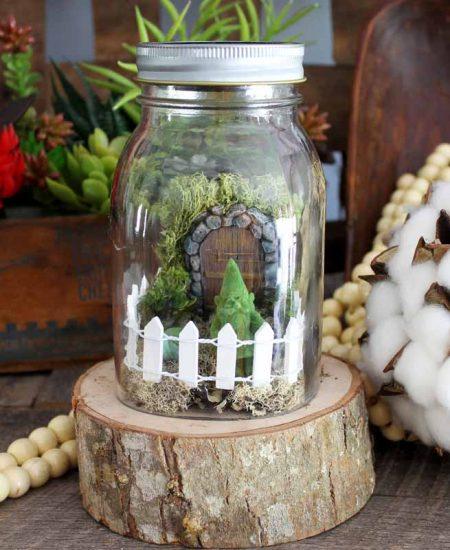 jar on a wood slice with a mini fairy garden inside