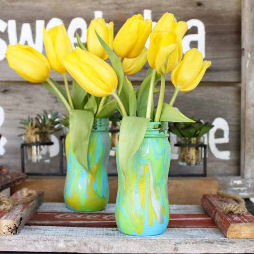 yellow flowers in mason jars that have marbled paint