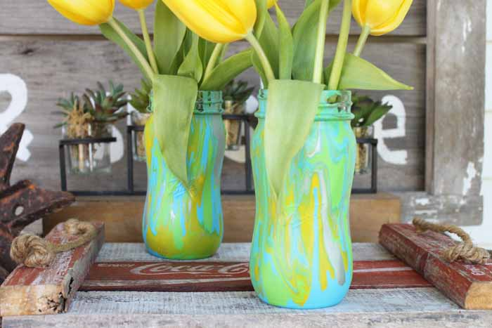 Try acrylic pouring on mason jars to make these spring vases! Paint pouring medium makes this a quick and easy project anyone would love!