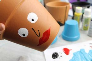 painting a face on a clay pot