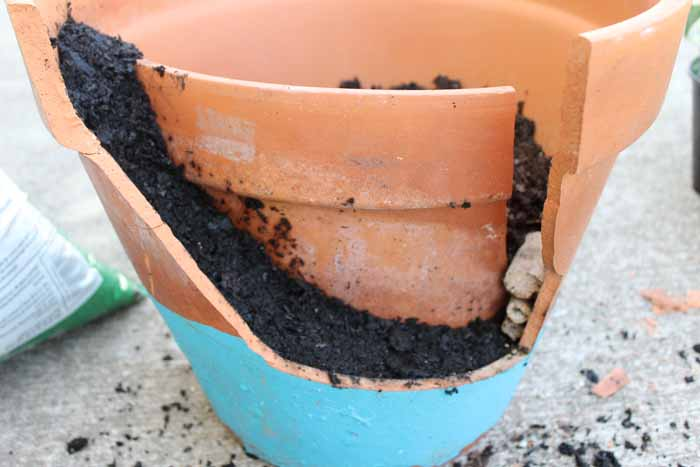 putting broken piece in the pot with dirt