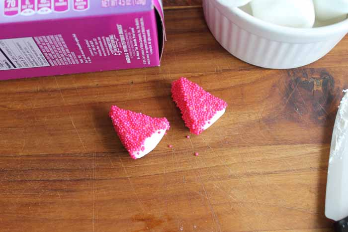 Cover the sticky sides of the marshmallows in sprinkles to make the unicorn ears
