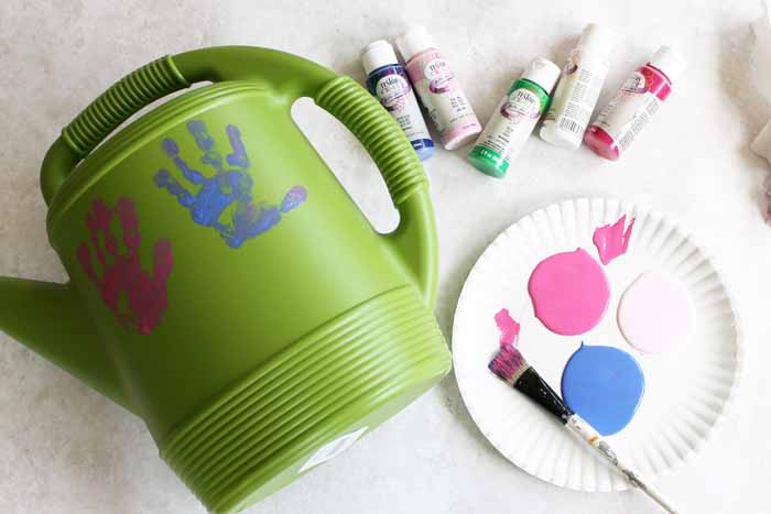 adding handprints onto a plastic watering can