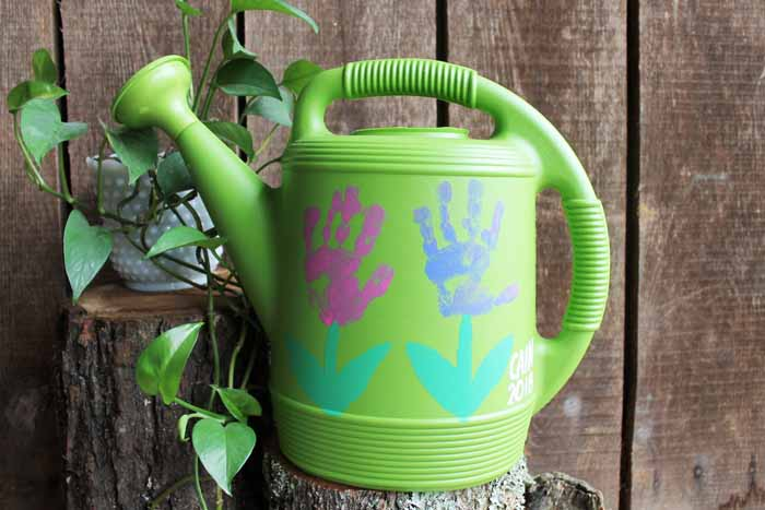 watering can with handprint flowers painted on it