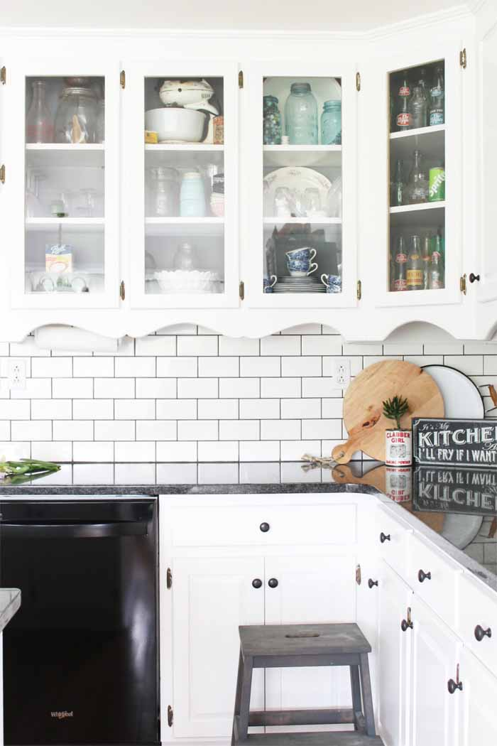 Glass front cabinets in a farm kitchen with mason jars and other rustic decor.