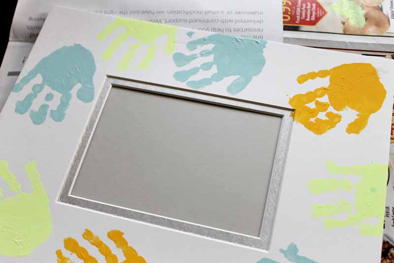 Add some handprint painting to a photo mat for a fun picture frame that dad will love this Father's Day! A quick and easy gift idea that toddlers and even babies can help make!