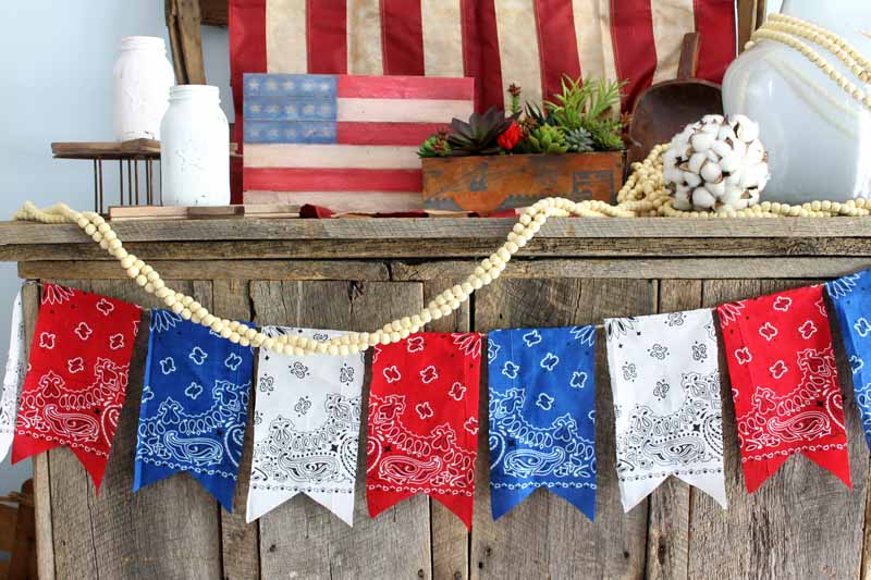 Add a patriotic bunting to your summer decor with bandanas! An easy DIY project that is perfect for 4th of July!