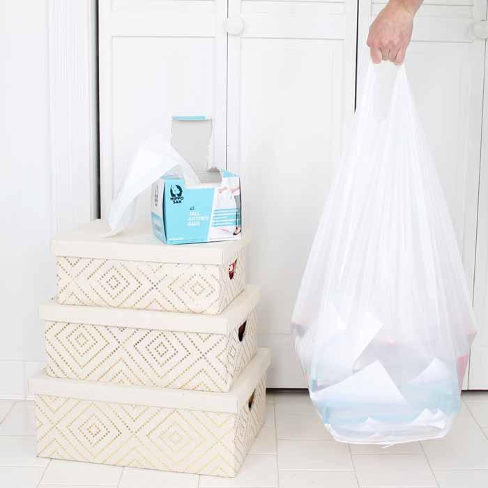 Three organizational boxes near trash bag of clutter