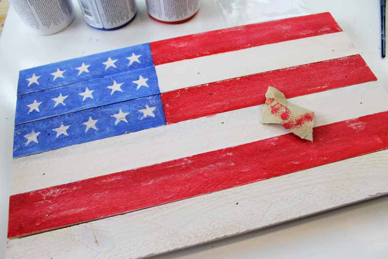 A rustic pallet flag being painted.