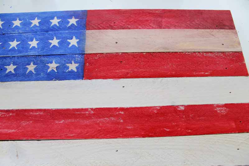 Distress painting on a rustic wooden flag.
