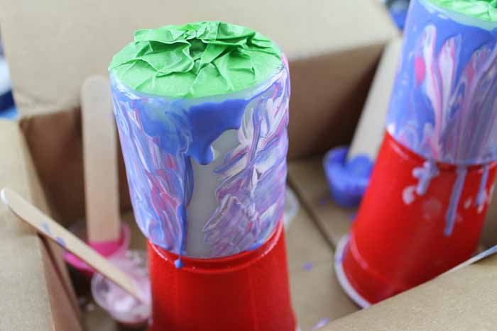 putting candle on a disposable cup for the paint to drip