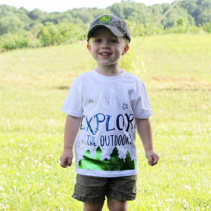 A young boy standing in a field wearing a camping shirt