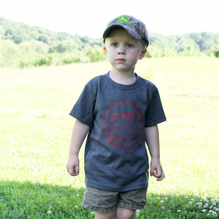 A little boy that is standing in the grass wearing a shirt about camping