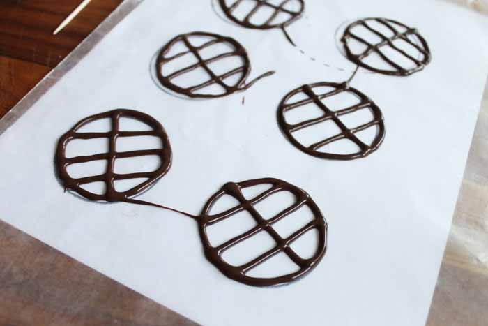 using a circle template under wax paper to make chocolate grill grates