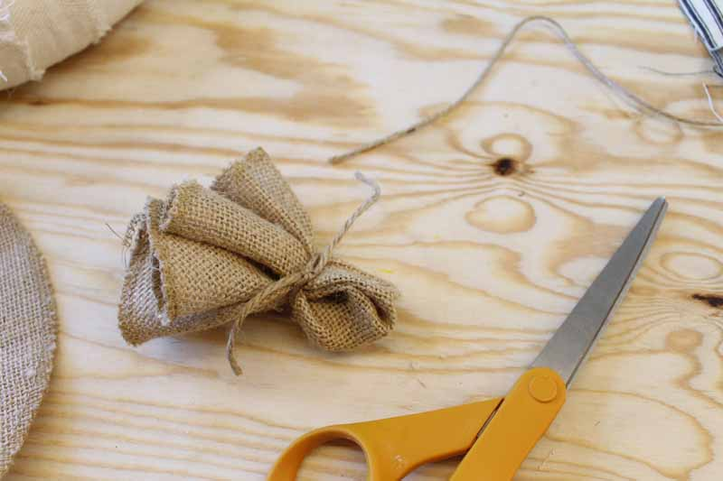 Gathering burlap circles to make burlap flowers for a wreath.