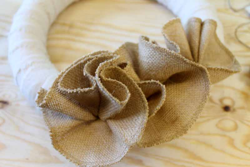 Using hot glue to secure burlap flowers to a wreath form.