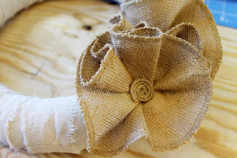 Putting centers in flower on a burlap wreath.