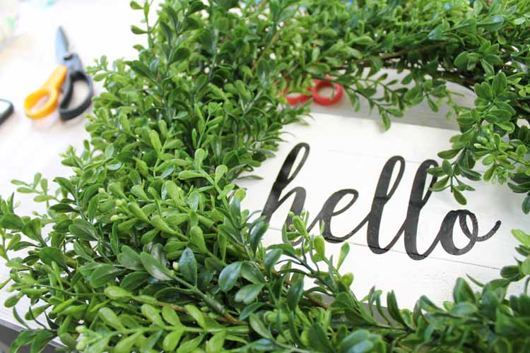 adding a green wreath to a white wood sign