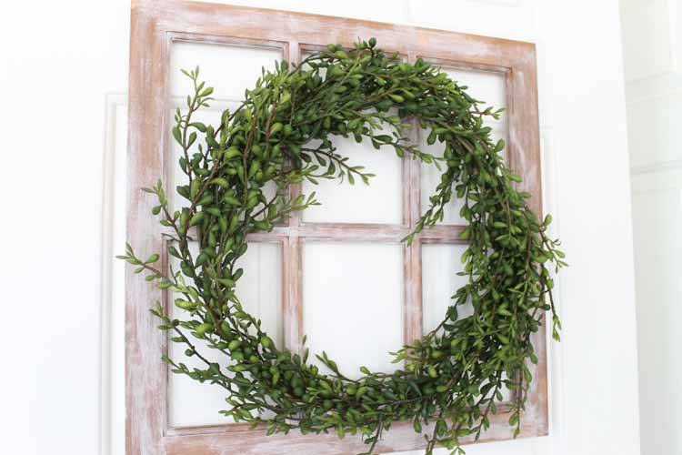a green wreath on a rustic window