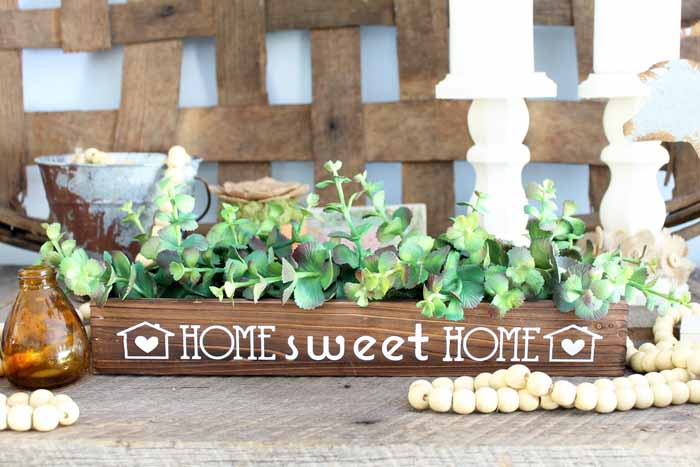 This wooden box centerpiece is perfect for your farmhouse style home! Make it in minutes with iron-on vinyl and your Cricut machine!