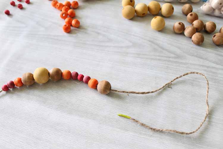 String wood beads to make this gorgeous beaded garland for fall! The wood stain technique makes them extra festive in autumn colors!