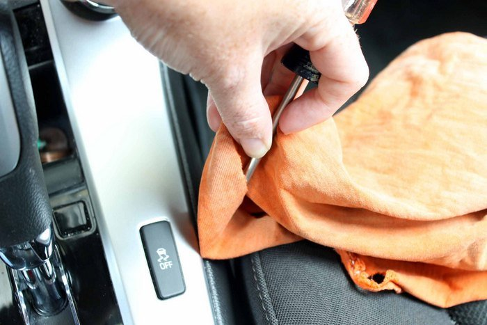 using a screwdriver and a rag for detailing a car