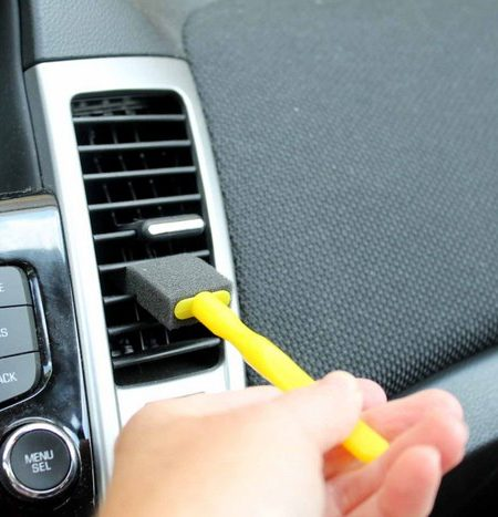 using a foam brush to detail a car