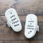 Make these DIY baby booties with some iron-on vinyl and your Cricut machine! A fun and easy baby shower gift idea!