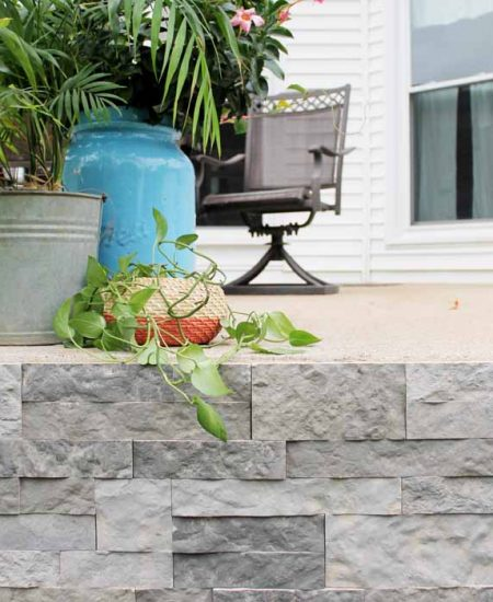 plants on a porch with stone veneer sides