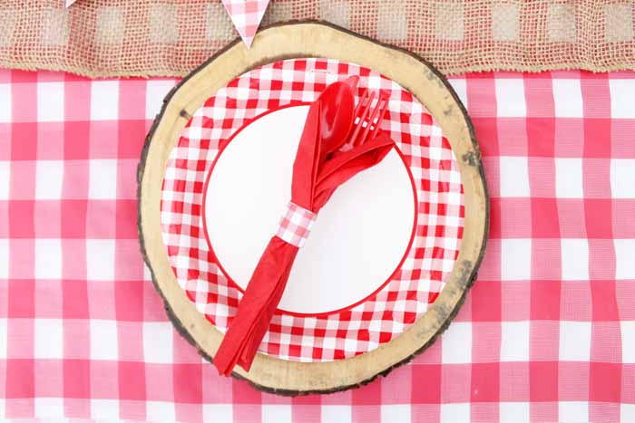 Festive checkered picnic plates set on wood place settings add a little rustic touch to your hot dog bar picnic