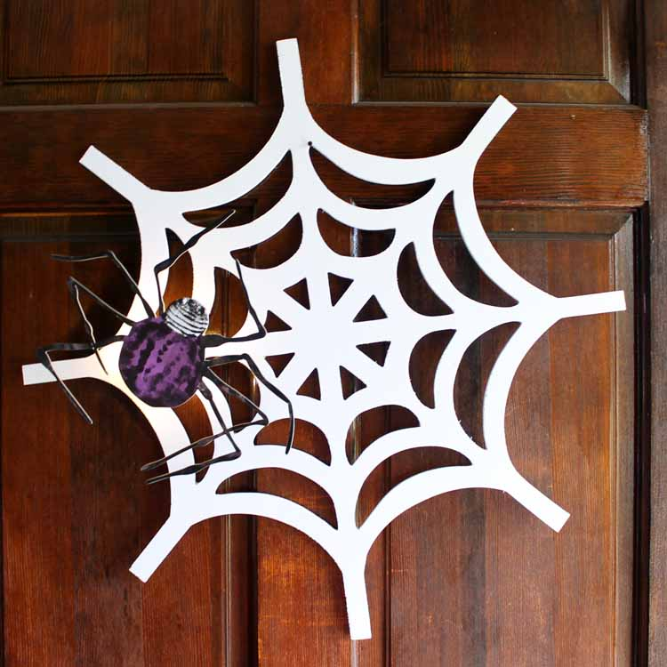 Make this DIY Halloween wreath with a spiderweb for your front door! A fun fall wreath that adds a little fright to your Halloween decorations! It even lights up! #halloween #wreath