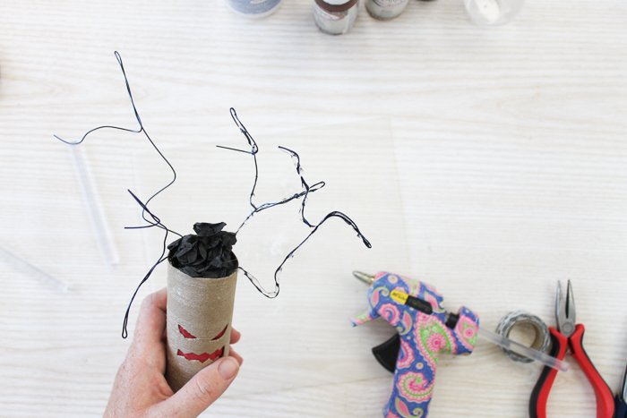 adding hot glue to wire tree branches