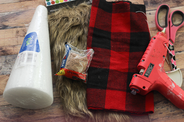 The supplies needed to make a Scandinavian gnome: a foam cone, faux fur, plaid fabric, and a hot glue gun