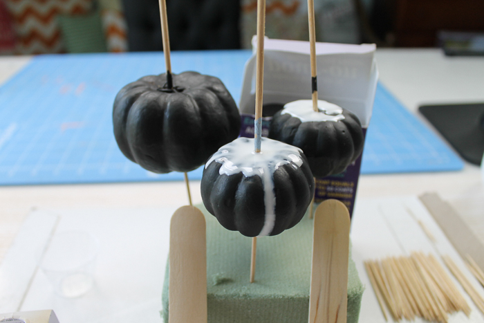 Pouring colored resin over black pumpkins to make marbled pumpkins.