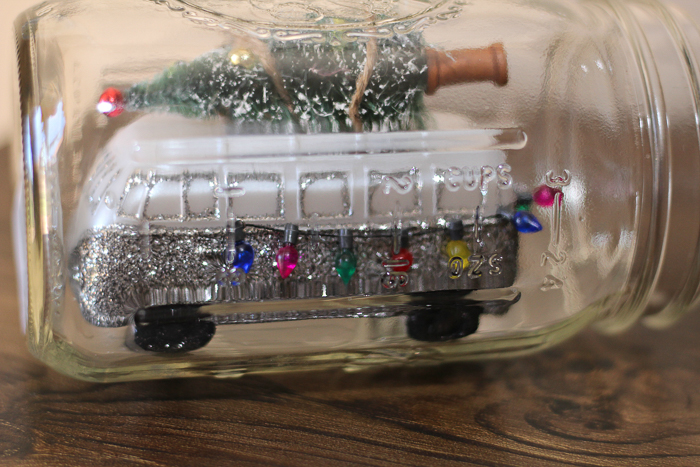 adding christmas ornaments inside of a mason jar