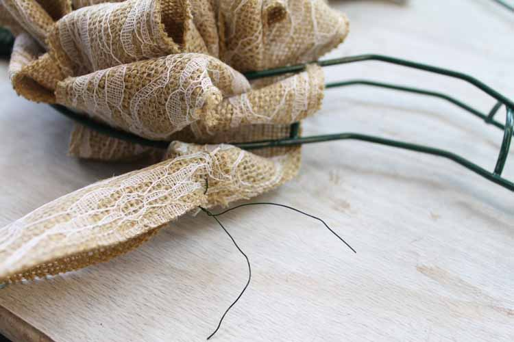 Attaching burlap to a heart wreath form.