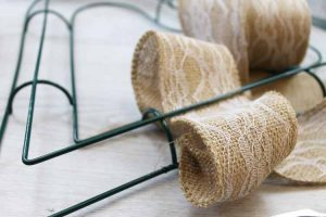Adding burlap ribbon to a wire wreath form.