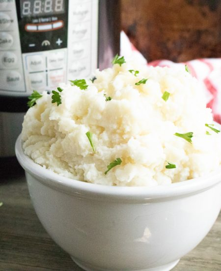A bowl of food on a table, with Mashed potato