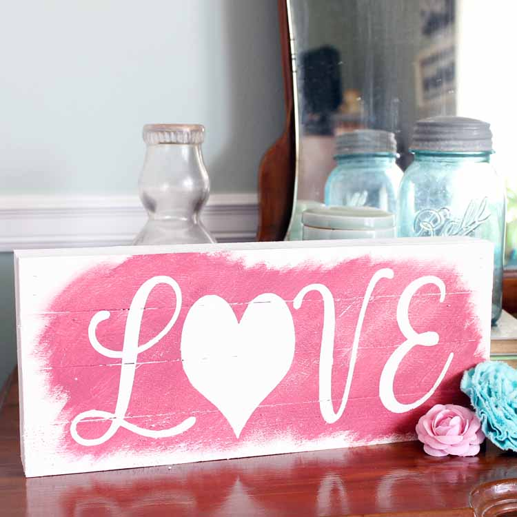 Make these reversible wooden signs with sayings! This one has winter on one side and Valentine's Day on the back. Use this same technique to make any wooden sign you want! #cricut #cricutmade