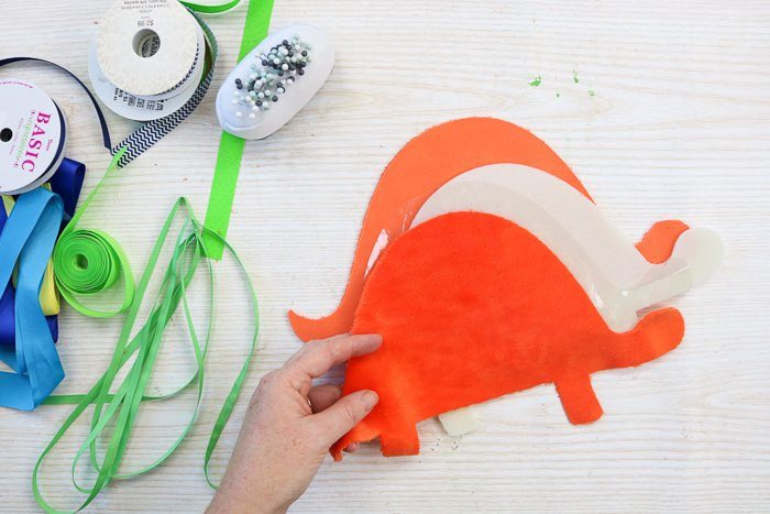 Cutting dinosaur shapes with a Cricut to make a baby tag blanket.