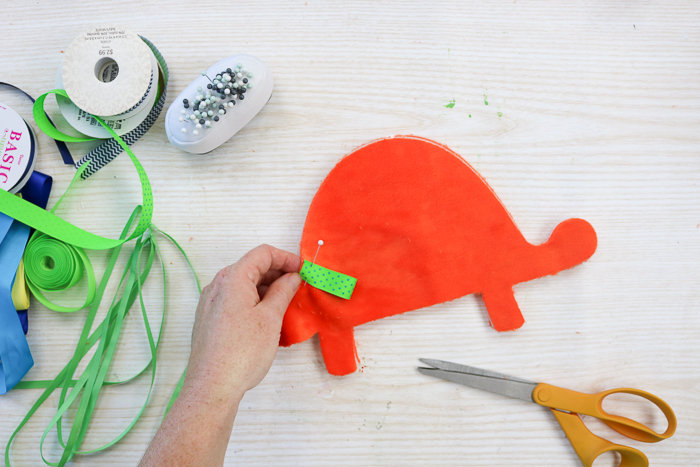 Adding ribbon to a dinosaur shape to make a baby tag blanket.