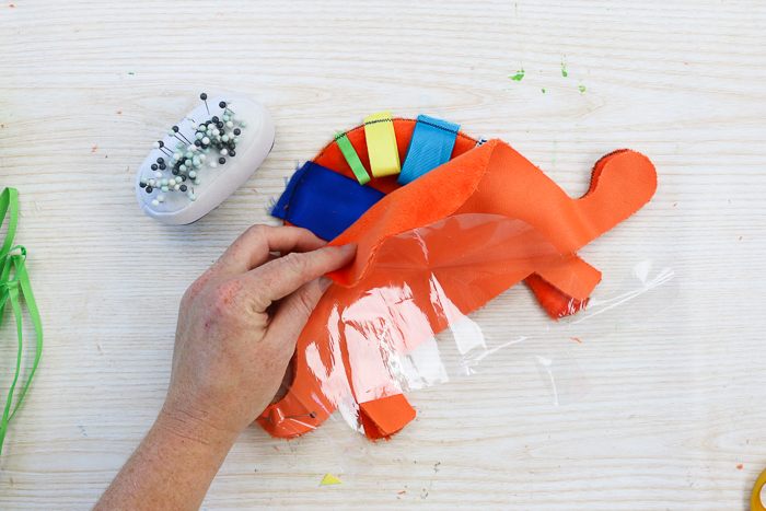 Assembling a baby tag blanket in a dinosaur shape.